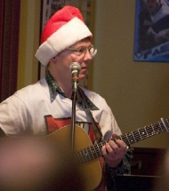 Eric playing guitar with Christmas hat on