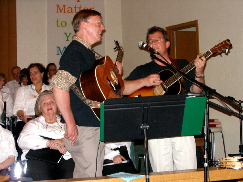Eric and Mark singing and playing guitar with choir in background