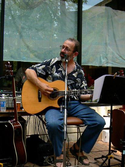Peter sitting playing guitar