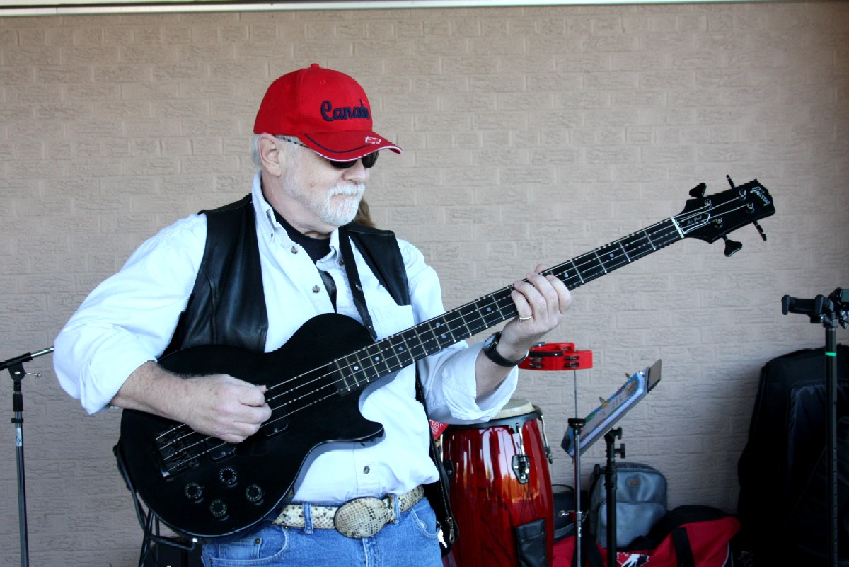 """Paul playing bass ans wearing a red """"Canada"""" baseball hat"""
