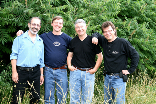 4 original Coyotes standing infront of sumac in park: Peter, Eric, Burke, Mark