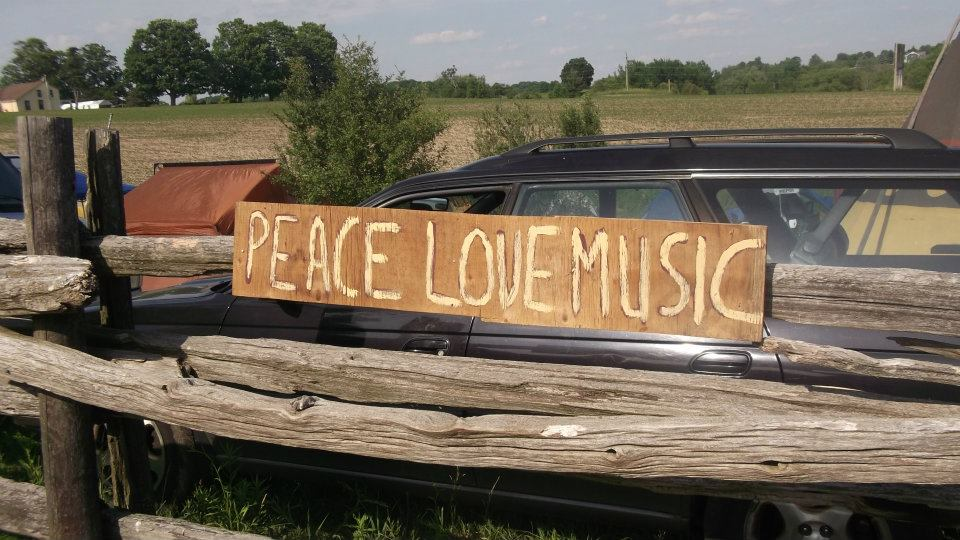 "fence with plywood sign: ""Peace Love Music"""