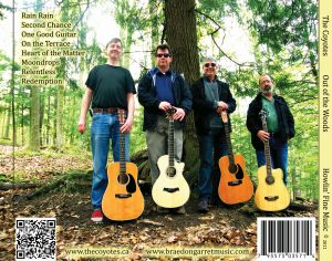 Eric, Mark, Burke, Peter standing with guitars in front of tree in forest