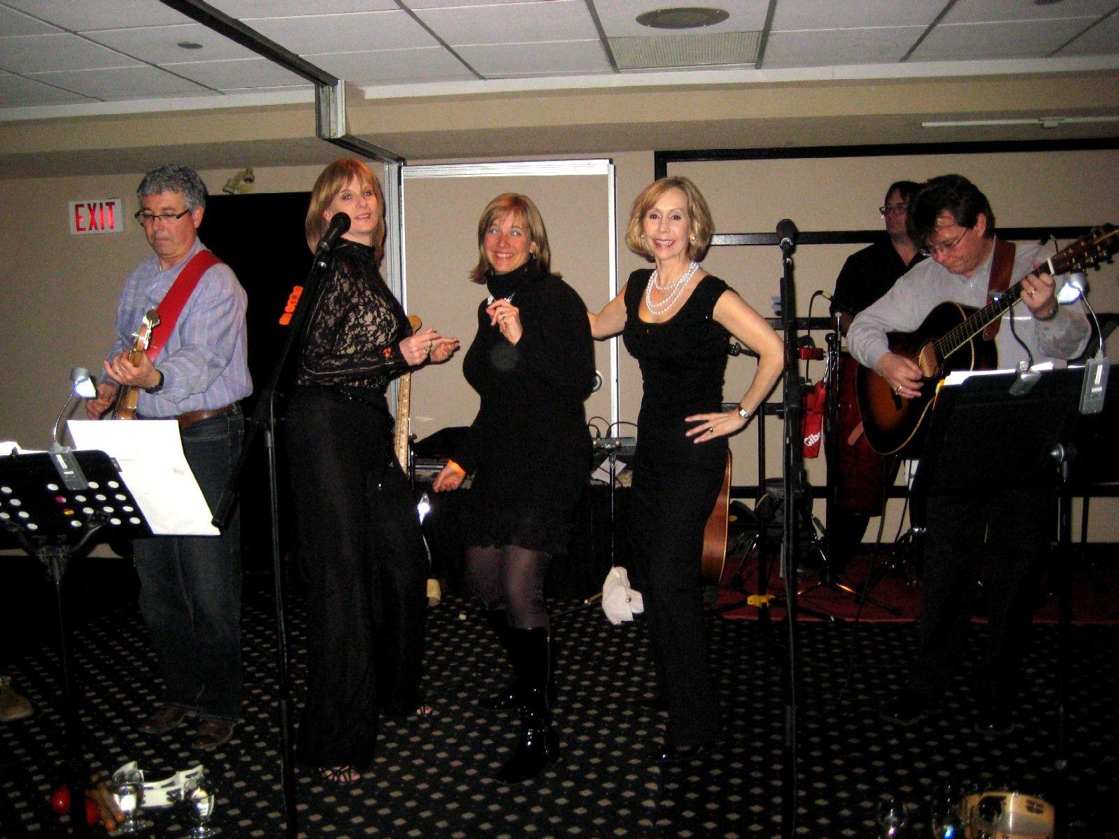 3 women singing/dancing accompanied by band